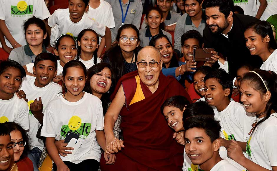 Tibetan spiritual leader Dalai Lama attended the Smile Foundation's initiative, 'The World of Children' in New Delhi on Sunday. Dalai Lama poses for a group photo with school students during the event. PTI