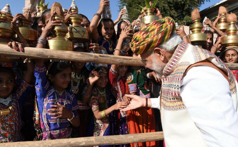 In a stinging attack on the Congress in poll-bound Gujarat, Modi said the upcoming Assembly election is a fight between trust on development and dynastic politics. Modi interacts with children at an election rally. Firstpost @Pallavi Rebbapragada