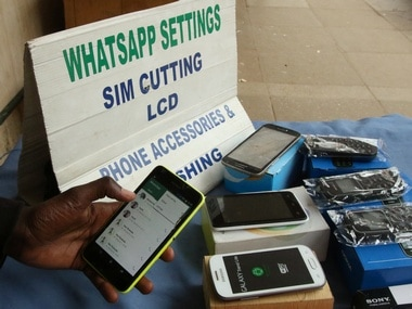 A street vendor adjusts the internet settings on a customer's mobile phone in Zimbabwe. Reuters.