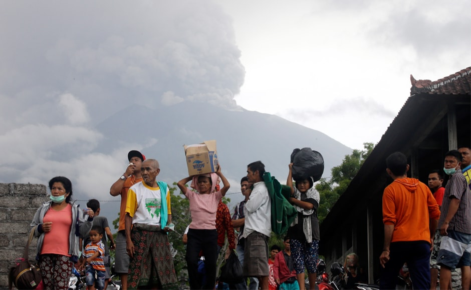 Villagers carry their belongings during an evacuation following the eruption of Mount Agung. About 25,000 people living close tothe mountain have already left their homes and evacuated since the volcanofirst started to spew smoke on Tuesday. AP
