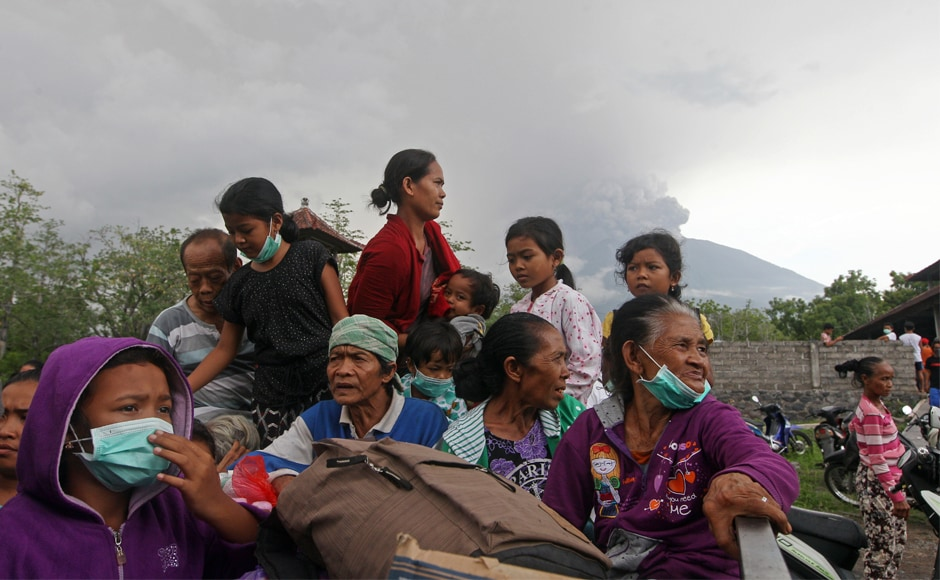 Villagers sit on a truck during an evacuation following the eruption of Mount Agung. National disaster agency spokesman Sutopo Purwo Nugroho also called for people to stay calm. AP