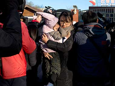 A woman leaves with a child after telling the media she came to withdraw the child from the RYB kindergarten in Beijing, China. AP