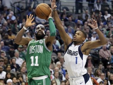Celtics' Kyrie Irving gets past Mavericks' Dennis Smith Jr for a shot-attempt in their match. AP