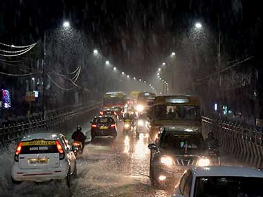 Vehicles move through a waterlogged road during heavy rain in Chennai on Friday. PTI