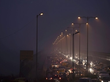 File image of people commuting through smog in New Delhi. PTI