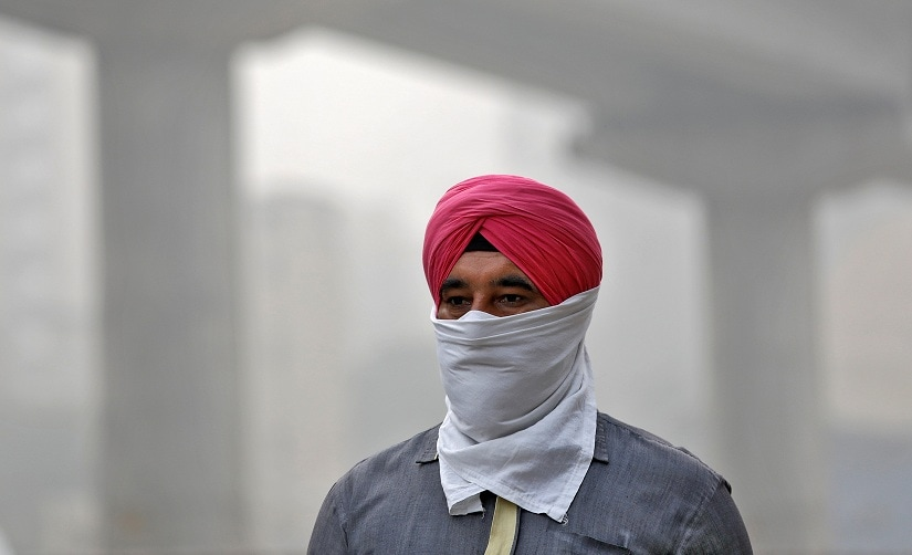 A man covers his face as he walks to work, in Delhi, India, November 7, 2017. REUTERS/Saumya Khandelwal - RC1400B61970