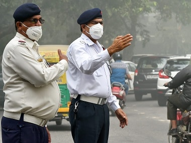 Traffic policemen wear masks to protect themselves from heavy smog in Delhi. PTI
