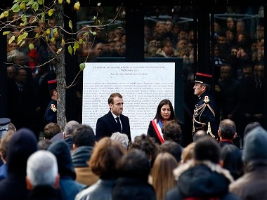 French President Emmanuel Macron, center left , flanked with Paris mayor Anne Hidalgo stand in front of a commemorative plaque with the list of victims at the Bataclan concert hall during a ceremony marking the second anniversary of the Paris attacks, Monday Nov.13 2017. In silence and tears, families of France's deadliest terrorist attacks stood alongside President Emmanuel Macron to honor the 130 people killed two years ago Monday, when Islamic State extremists attacked the City of Light. (AP Photo/Francois Mori)