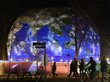 People pass the German pavilion in the shape of the earth during the COP 23 Fiji UN Climate Change Conference in Bonn, Germany. AP