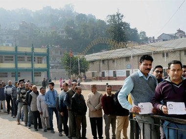 Voters in a queue show their voter identity card at a polling booth in Mandi, Himachal Pradesh on Thursday. PTI