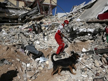 A rescue worker searches the debris on the earthquake site. AP