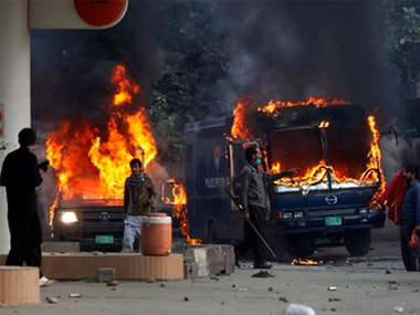 Pakistani protesters gather next to burning police vehicles after setting on fire them during a clash in Islamabad. AP