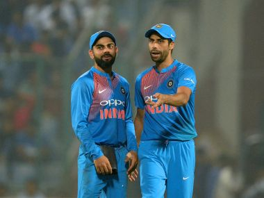Indian captain Virat Kohli (L) and Ashish Nehra speak during the first  T20 against New Zealand. AFP