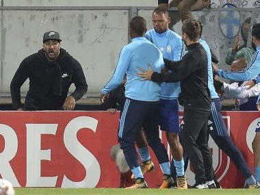 Marseille's Patrice Evra, center left, is led away by his teammate Rolando after a scuffle with Marseille supporters who trespassed into the field before the Europa League group I soccer match between Vitoria SC and Olympique de Marseille at the D. Afonso Henriques stadium in Guimaraes, Portugal, Thursday, Nov. 2, 2017. Evra was shown a red card before the start of the match for his involvement in the incident. (AP Photo/Luis Vieira)