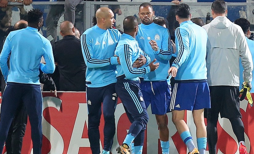 Marseille's Patrice Evra is dragged away by his teammates during a scuffle with the club's supporters. AP