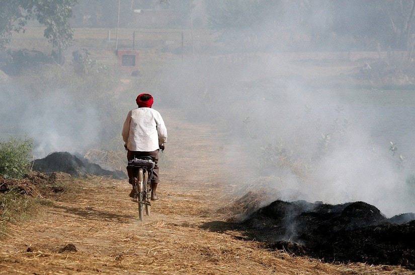 A man paddles his cycle amidst smoke billowing from burning paddy waste stubble in a field on the outskirts of Amritsar, India November 8, 2016. REUTERS/Munish Sharma - D1BEULQOGFAA