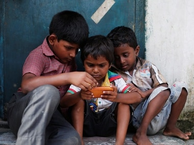 Children watching on a mobile phone in rural areas of India. Reuters