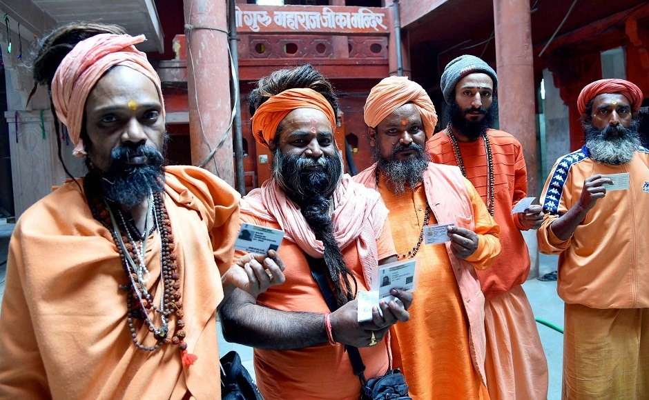 Sadhus display their voter identity cards before casting their votes. About 4,200 policemen, 1,000 home guards and eight companies of Provincial Armed Constabulary have been deployed for poll duty. PTI