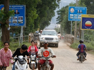 People travel past the signboard logos of the opposition Cambodia Rescue Party. AP
