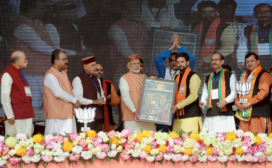 Modi honoured by BJP leader Anurag Thakur during the election rally at Una on Sunday. PTI