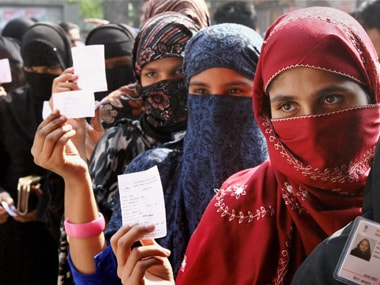 Burqa-clad voters wait to cast their votes for local body elections, at a polling station. PTI