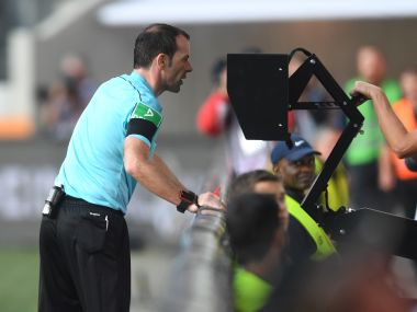 Referee Marco Fritz checking the Video Assistant Referee (VAR) during a Bundesliga match between FC Augsburg and Borussia Dortmund. AFP