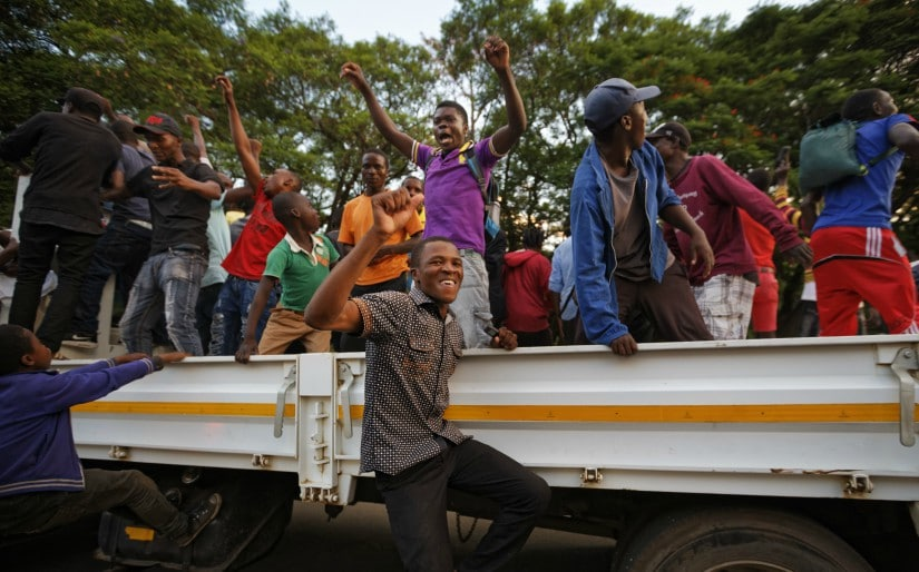 Zimbabweans celebrate outside the parliament building immediately after hearing the news that President Robert Mugabe had resigned on Tuesday. AP