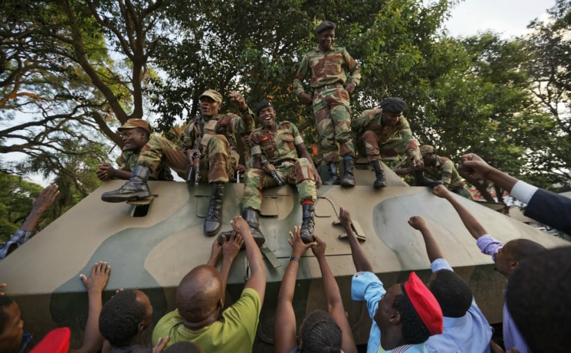 Zimbabweans reach out to touch and thank army soldiers, as they celebrate outside the parliament building on Tuesday. AP