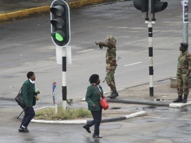 Armed soldiers stand on the road leading to President Robert Mugabe's office in Harare, Zimbabwe. AP