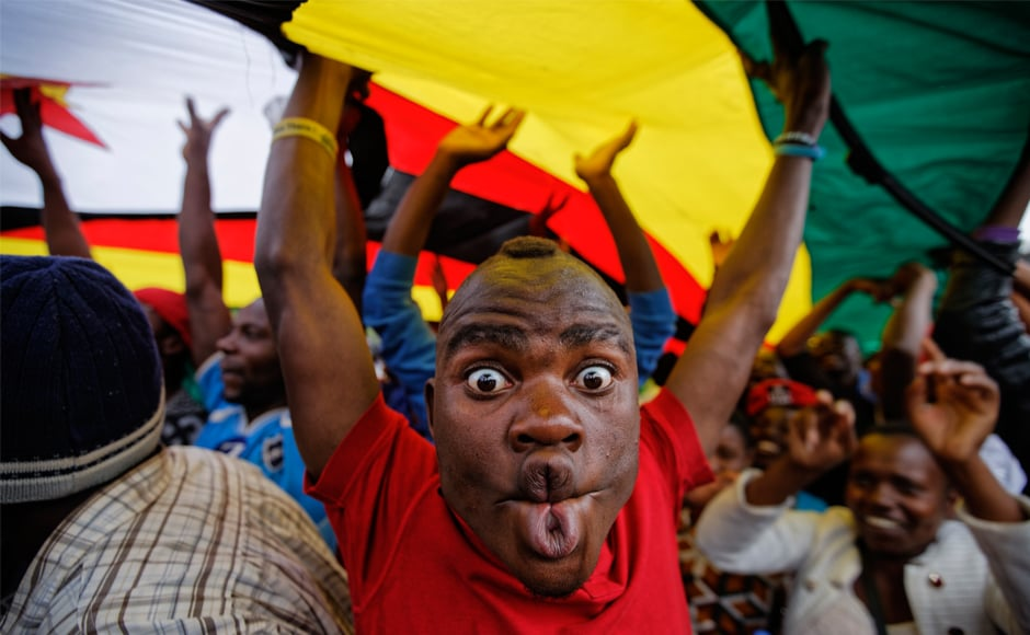 A happy protester pulls a face as he and others stand under a large national flag, at the demonstration of tens of thousands at Zimbabwe Grounds in Harare. AP