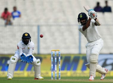 India's Cheteshwar Pujara plays a shot as Sri Lanka wicket-keeper Niroshan Dickwella looks on during the third day of the first Test in Kolkata. AFP