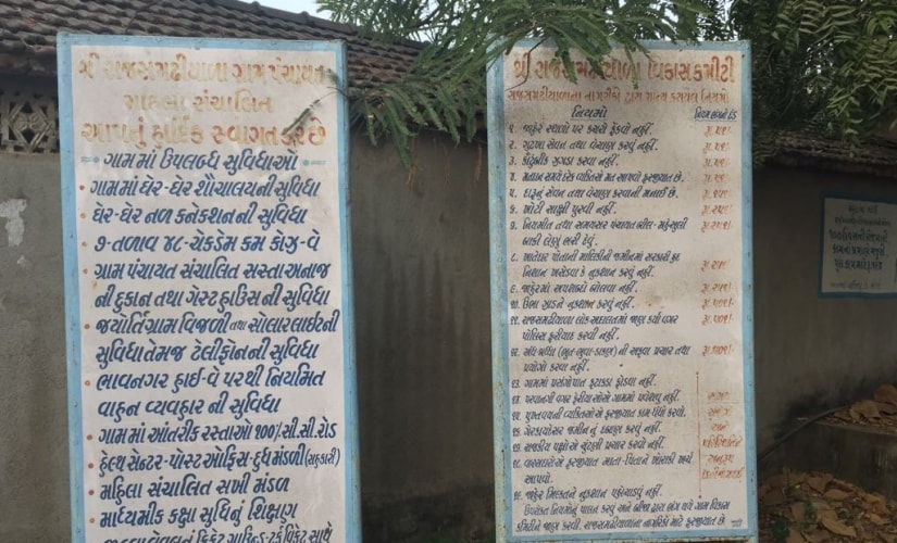 The two boards listing the rules and facilities in Rajsamadiyala village. Firstpost/Amitesh Singh