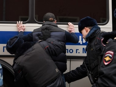 Police officers search a man during a protest in Moscow. AP