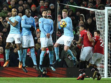 The Manchester City The defensive wall (L-R) Manchester City's English midfielder Fabian Delph, Manchester City's French defender Eliaquim Mangala, Manchester City's English defender Kyle Walker and Manchester City's Belgian midfielder Kevin De Bruyne jumps to try to block a free kick during the English Premier League football match between Manchester United and Manchester City at Old Trafford in Manchester, north west England, on December 10, 2017. / AFP PHOTO / Oli SCARFF / RESTRICTED TO EDITORIAL USE. No use with unauthorized audio, video, data, fixture lists, club/league logos or 'live' services. Online in-match use limited to 75 images, no video emulation. No use in betting, games or single club/league/player publications. /