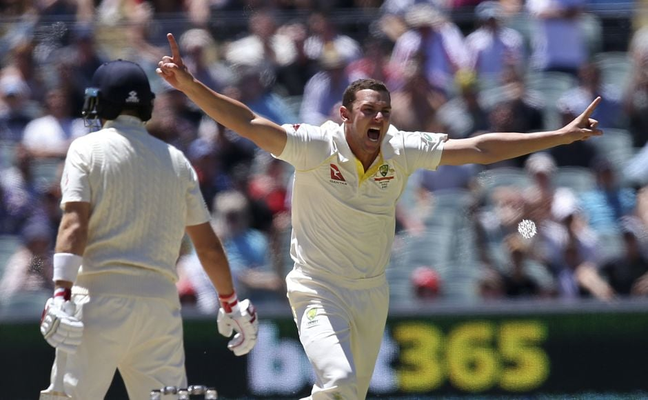 Australia's Josh Hazlewood, right, celebrates the wicket of England's Joe Root, left, caught behind for 67 runs during Day 5. AP