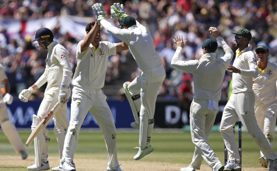 Australia's Mitchell Starc, second left, celebrates with teammates after taking the wicket of England's Craig Overton, left, during the fifth day of their Ashes Test match in Adelaide.<br />AP