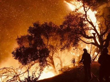 Firefighters knock down flames as they advance on homes in California. AP