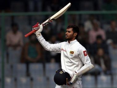 Sri Lanka's Dhananjaya De Silva raises his bat to celebrate scoring a century during the fifth day of their third Test against India. AP