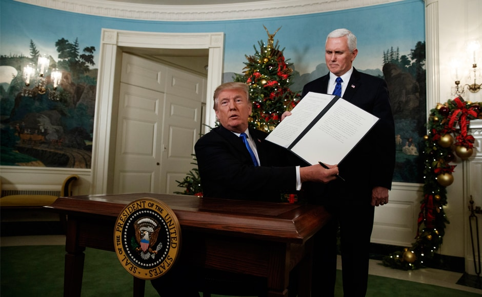 Donald Trump, accompanied by Vice-President Mike Pence, holds up a signed proclamation recognising Jerusalem as the capital of Israel. He also said the United States would move its embassy from Tel Aviv to Jerusalem, though he set no timetable. AP