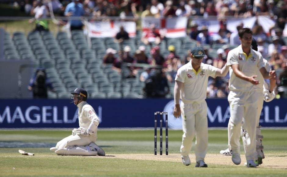 England's Craig Overton, left, falls to his knees after being hint by a delivery from Australia's Pat Cummins, right. (AP Photo/Rick Rycroft)