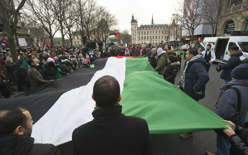 Demonstrators hold a Palestinian flag as they stage a protest against US president Donald Trump's decision to recognise Jerusalem as the capital of Israel in Paris. AP