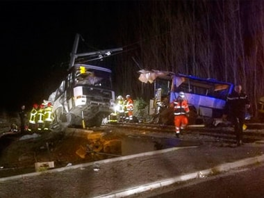 rescue workers help after a school bus and a regional train collided in the village of Millas, southern France. AP
