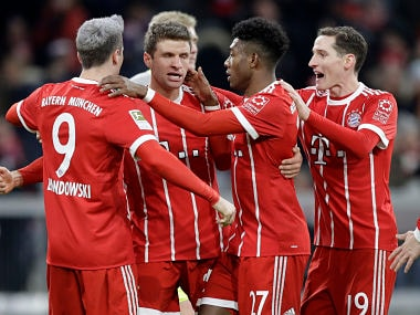 Bayern's Robert Lewandowski , left, celebrates with team mates after scoring his side's opening goal during the German Soccer Bundesliga match between FC Bayern Munich and 1.FC Koeln in Munich, Germany, Wednesday, Dec. 13, 2017. (AP Photo/Matthias Schrader)