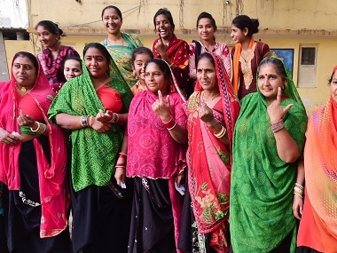 Local women show their ink-marked fingers after casting their vote during the first phase of Gujarat election. PTI
