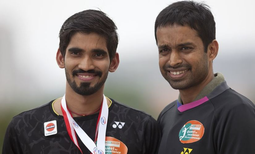 Indian Badminton player Srikanth Kidambi along with his coach Pullela Gopichand pose for photographs after a press conference at the Pullela Gopichand Academy in Hyderabad, India, Tuesday, June 27, 2017. Srikanth won the Indonesian Open and the Australian Open super series men's singles titles in the last two weeks. (AP Photo/Mahesh Kumar A.)