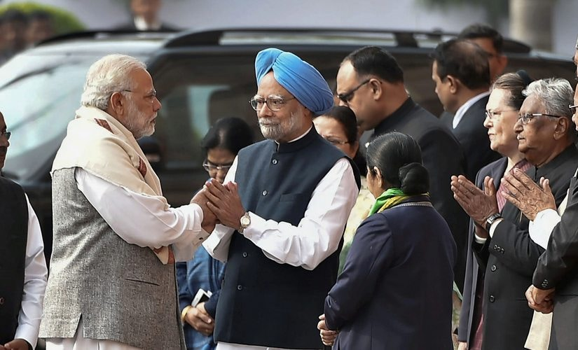 Prime Minister Narendra Modi and former prime minister Manmohan Singh exchange greetings during the tribute paying ceremony for the martyrs of 2001 Parliament attack on its 16th anniversary, at Parliament House. PTI