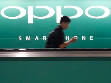A commuter using his mobile phone passes an advertisement of Chinese smartphone maker Oppo. Image: Reuters