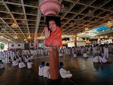 Devotees sit inside the ashram to pay their last respects to Sri Sathya Sai Baba at Puttaparti. Reuters