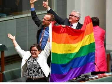 Members of parliament, from left, Cathy McGowan, Adam Brandt and Andrew Wilkie celebrate the passing of the Marriage Amendment Bill in the House of Representatives at Parliament House in Canberra. AP