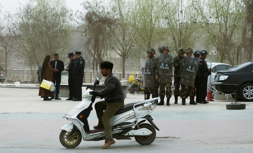 In this file image, Police officers check the identity cards of people as security forces keep watch in a street in, Xinjiang Uighur Autonomous Region, China. Reuters